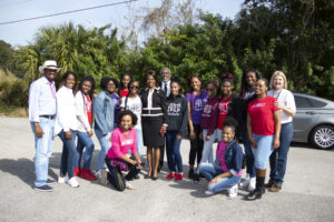 Mayor Demings, his wife, and a group of African American young women posing for a photo at the Apopka Parade.