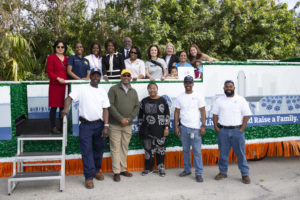 The Mayor, his wife, and Orange County employees standing in front of and on a stationary Orange County parade float.