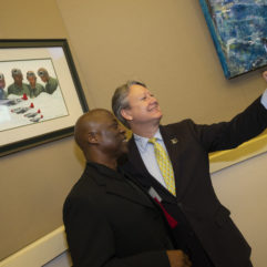 Two men taking a picture of themselves next to a piece of art inside the Chambers.