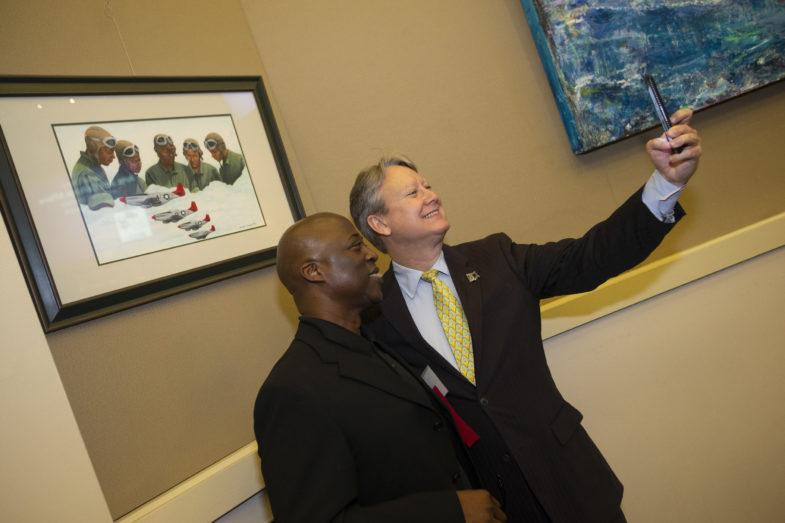 Dos hombres tomándose una foto cerca de una obra de arte dentro de las Cámaras.