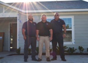 Three builders, men, stand together for a photo.