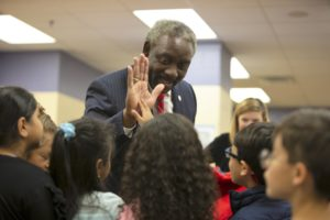 Mayor Demings giving a high-five to a young girl while surrounded by children in a classroom.
