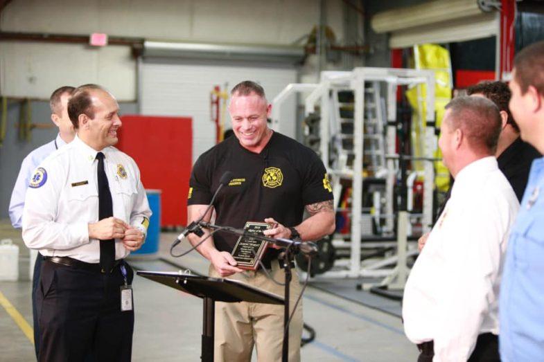 Desde el interior de la Estación de Bomberos, el bombero Jason Wheat sonríe con el Premio al Bombero del Año en la mano. El Jefe del Cuerpo de Bomberos,Otto Drodz, y otros líderes sonríen mientras Jason se acerca al podio.