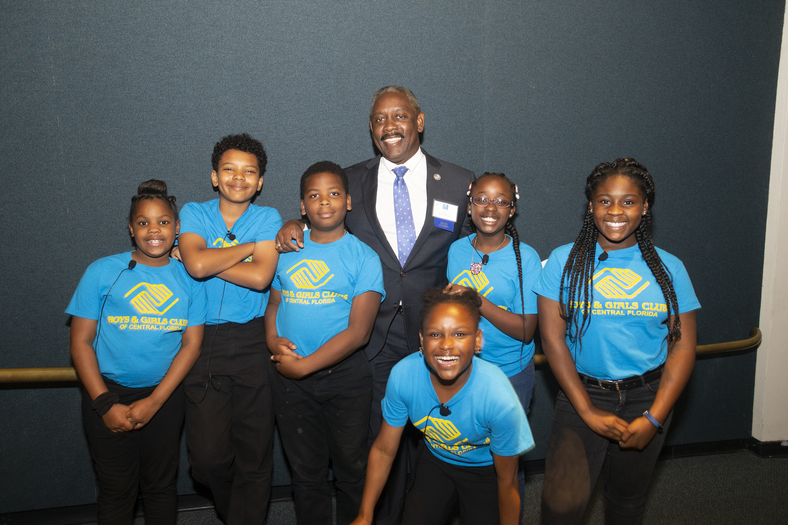 Mayor Demings posing for a photo and embracing the six children surrounding him. The children are wearing their Boys and Girls club t-shirt and are elated to be taking a photo.