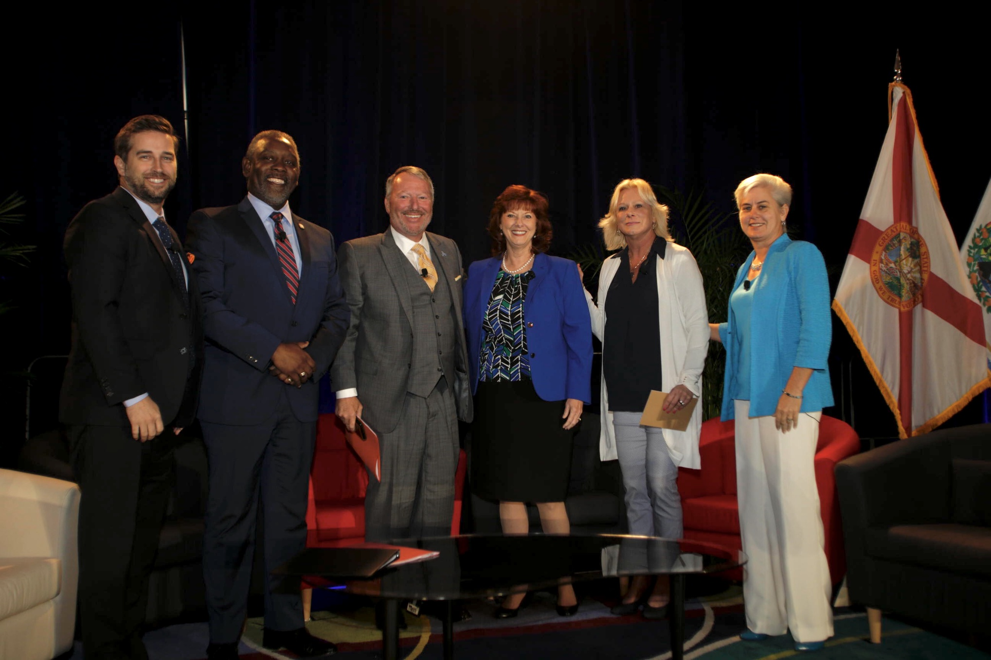 A panel, Regional Topics and Vision, is on stage. It consists of Tim Giuliani, Mayor Demings, Mayor Dyer, Chair Campione, Chair Carey, and Chair Grieb. They are on stage sitting in a semi circle around a table, with the state and county flags in the background.