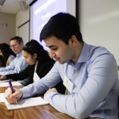 A close up shot of a student panelist focusing on a sheet of paper with pen in hand, as are the three other students and employees sitting alongside him.