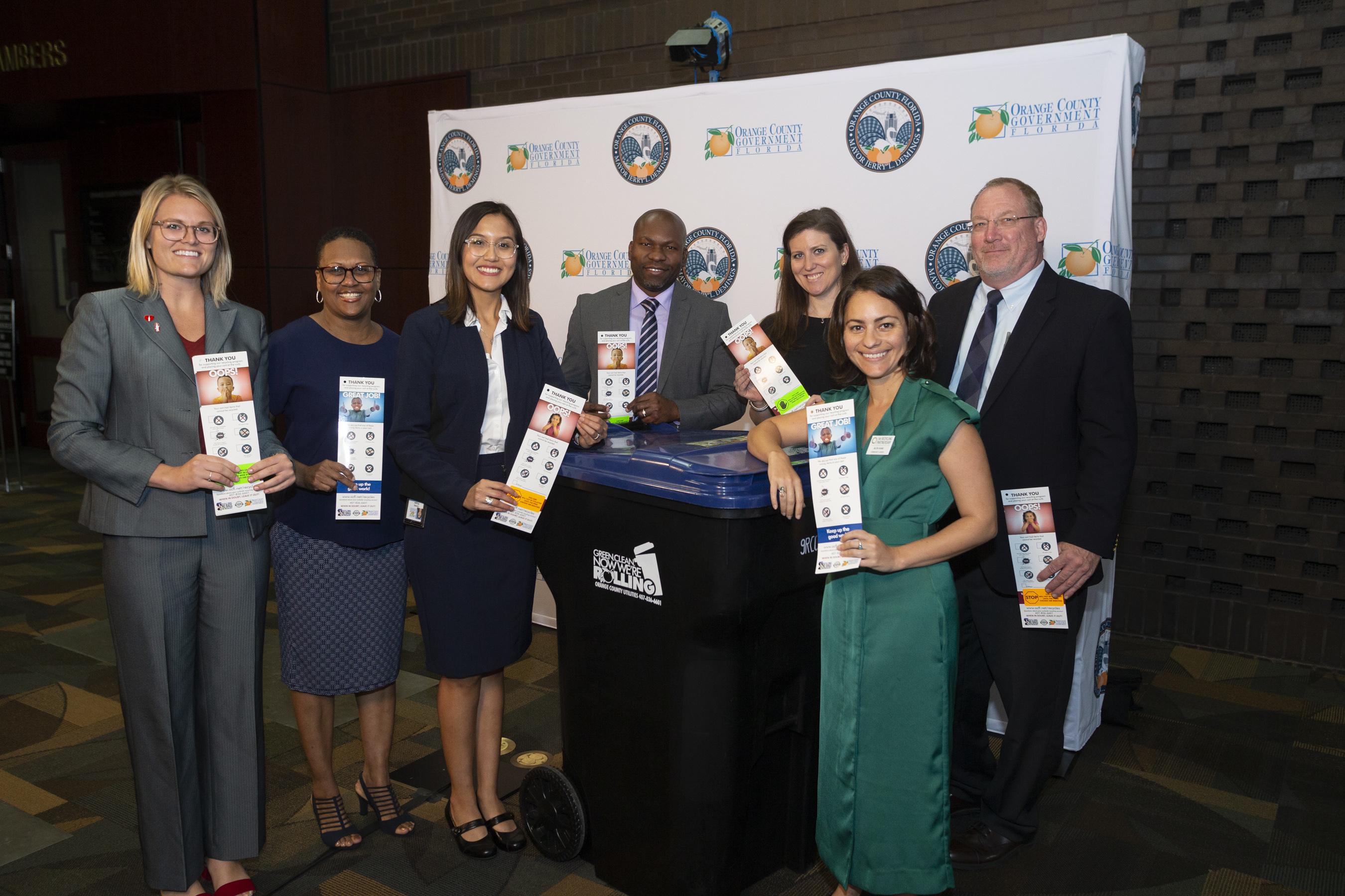 Left to right, Jennifer Baugher with Coca-Cola Florida, Marchelle Allen, Cindy Harpel and Allen Cole with Orange County Utilities, Shannon Sellman with Coca-Cola corporate, Alita Kane with The Recycling Partnership and David Gregory with Orange County Utilities, posing for a photo holding recycling flyers.