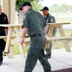Four corrections officers carrying a picnic table with benches. They are outside under a pavilion.