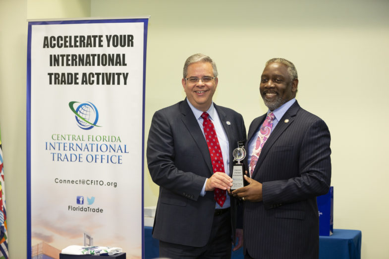 Central Florida International Trade Office Program Manager Christopher Leggett stands with Orange County Mayor Jerry L. Demings as they both hold an award.