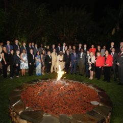 Mayor Demings, Orange County Staff, and foreign Diplomats stand in a semi-circle around a lit fire pit. There are over two dozen individuals smiling for the photo.