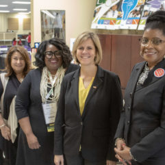 Five Head Start staff members, all women, standing in a diagonal line for a photo. They are smiling and are inside an office setting.