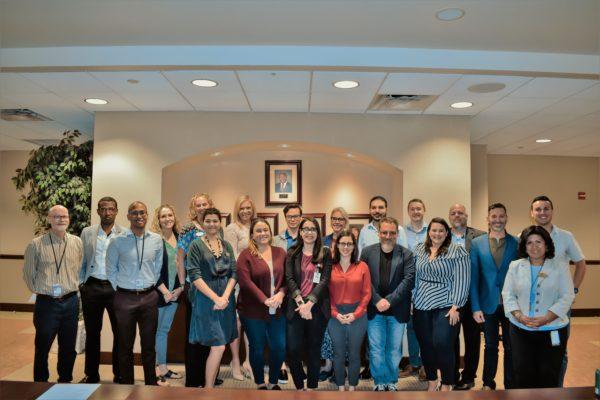 Un grupo de veintepersonas influyentes de la tecnología y los medios sociales posan para una foto dentro de la sala de conferencias.