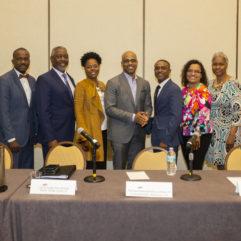 El Alcalde Demings posa para la foto junto con los miembros del panel. Hay nueve hombres y mujeres con atuendo formal parados uno al lado del otro.