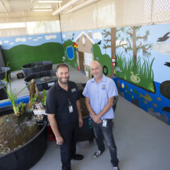 Two men inside a building, standing by six car-size containers full of water and fish. Behind them is a newly painted mural depicting a lake and wildlife.