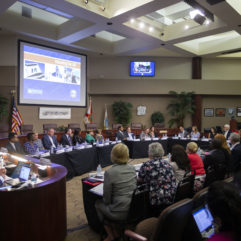 Inside of the brightly lit Board of County Commissioners Chambers the Housing for All Task Force members sit in front of the dais at tables arranged in an oval shape as they discuss the items on the agenda. Individuals from the public are seated in the audience section.