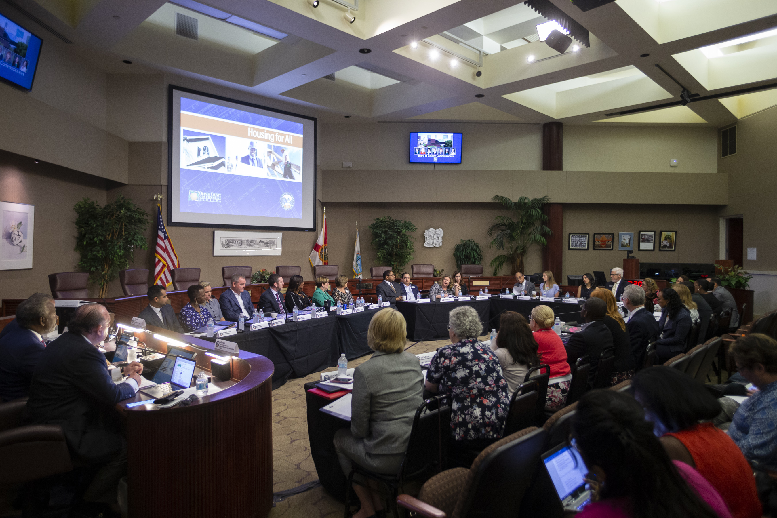 En el interior de las Cámaras de la Junta de Comisionados del Condado, completamente iluminado, los miembros delEquipo de Trabajo de Viviendas para Todos permanecen sentados frente al estrado con mesas dispuestas en forma de óvalo mientras discuten los temas de la agenda. Las personas del publico están sentadas en el sector destinado para la audiencia.