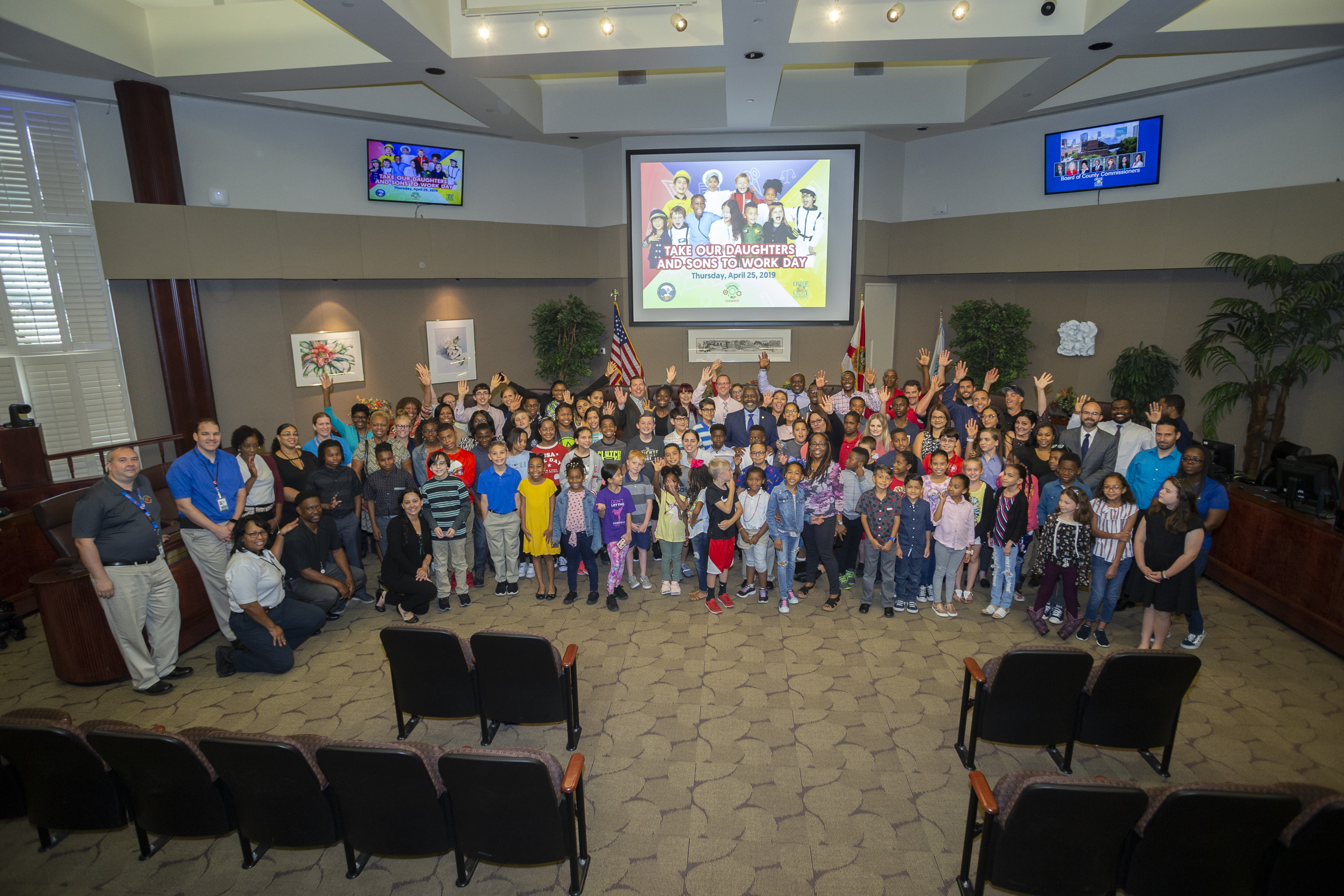 A group photo of children and orange county staff in the Board of County Commissioner's chambers. Mayor Demings is standing in the middle of the crowd of smiling children.
