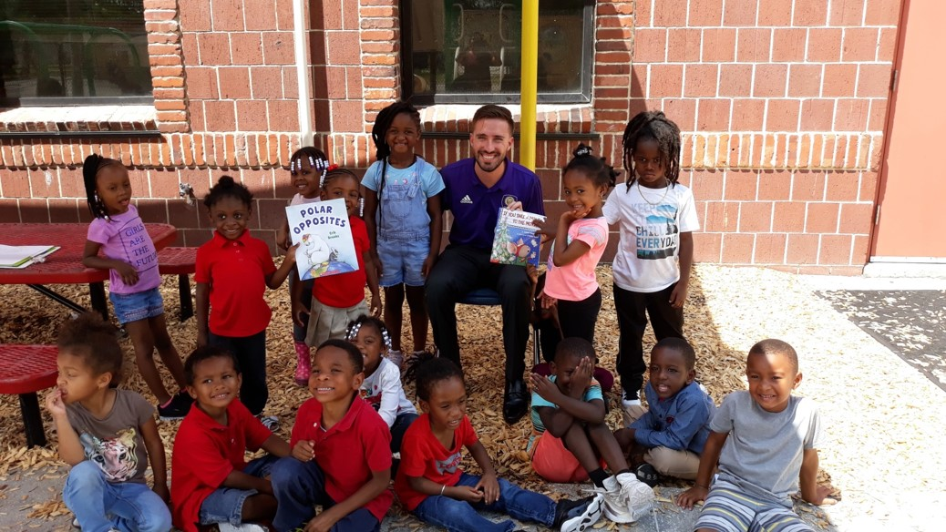 Sam Fowler, Member Services representative for Orlando City Soccer, is sitting outside with a dozen young children, some of whom are holding up books.