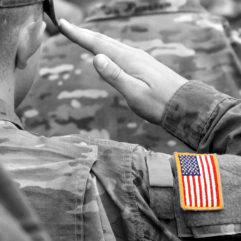 A close up photo of a man in a camouflage uniform saluting. On his sleeve the American flag is shown.