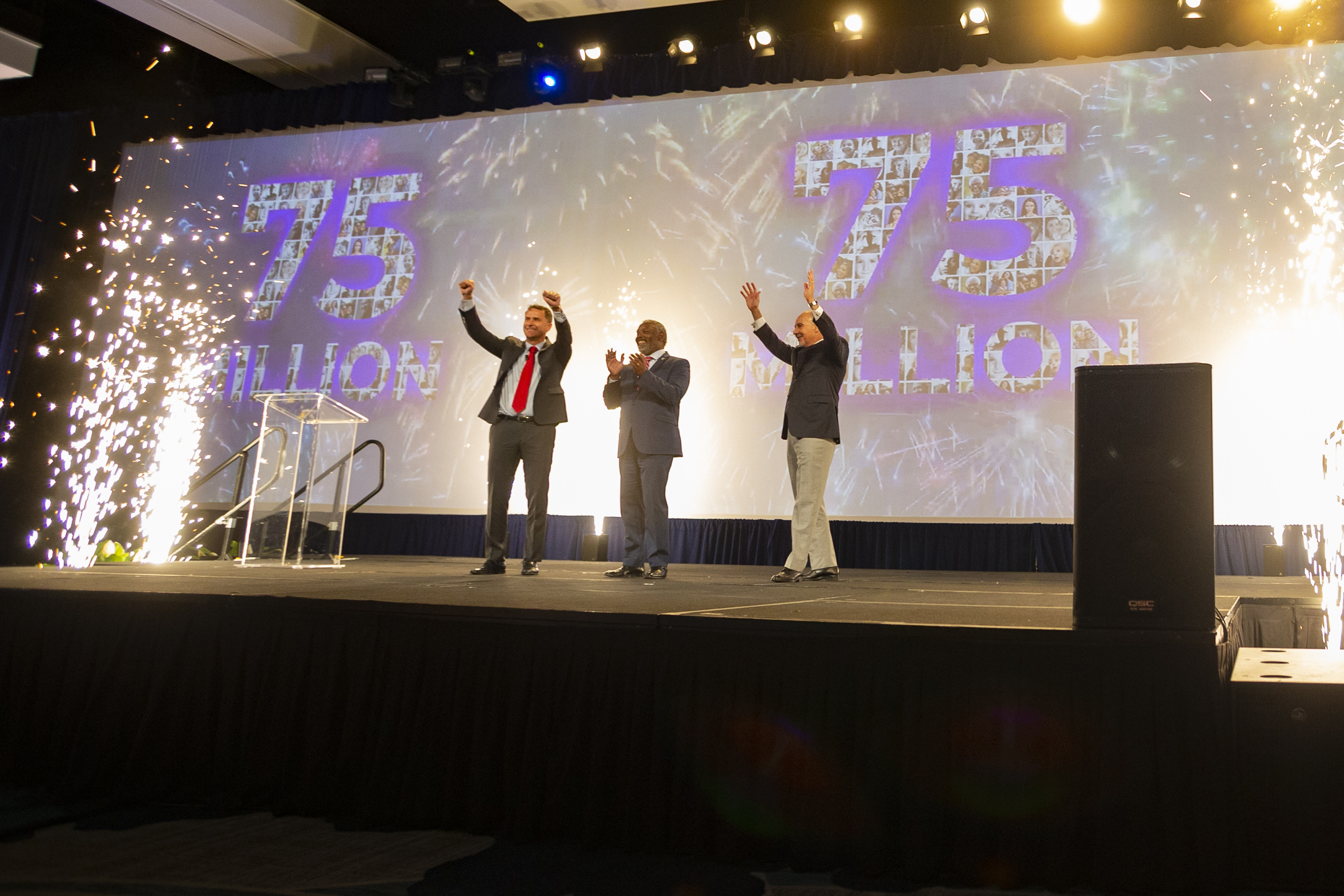 """El Alcalde Demings junto a otros dos hombres en el escenario. Detrás de ellos puede leerse """"75 millones"""" en la pantalla gigante."""