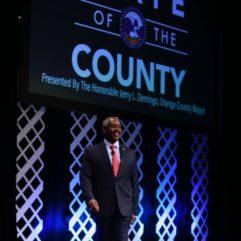 """El Alcalde Demings parado en el escenario. Se puede leer """"Estado del Condado"""" en el fondo."""