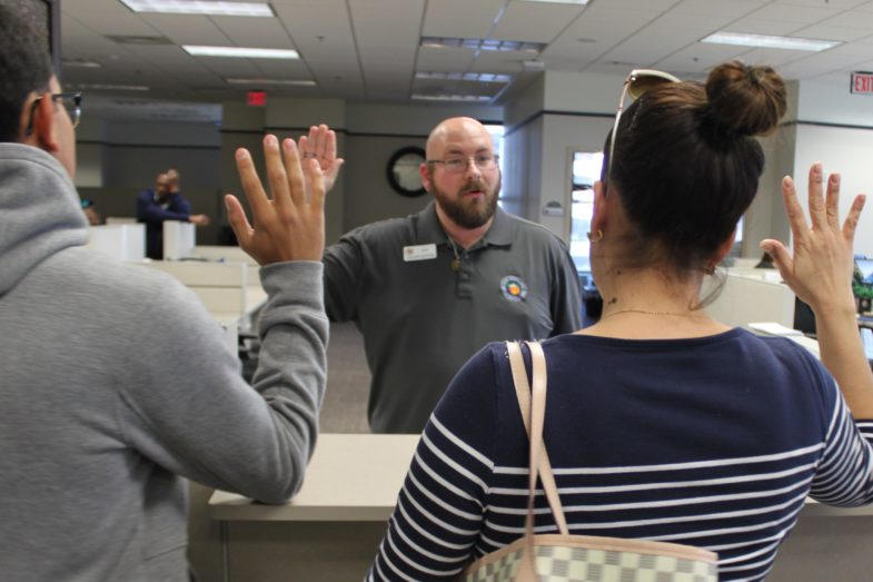 A man and a woman stand before a clerk of the courts with their hands raised, palms out