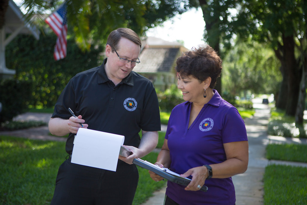 Two Orange County Tax Collector employees canvasing a neighborhood