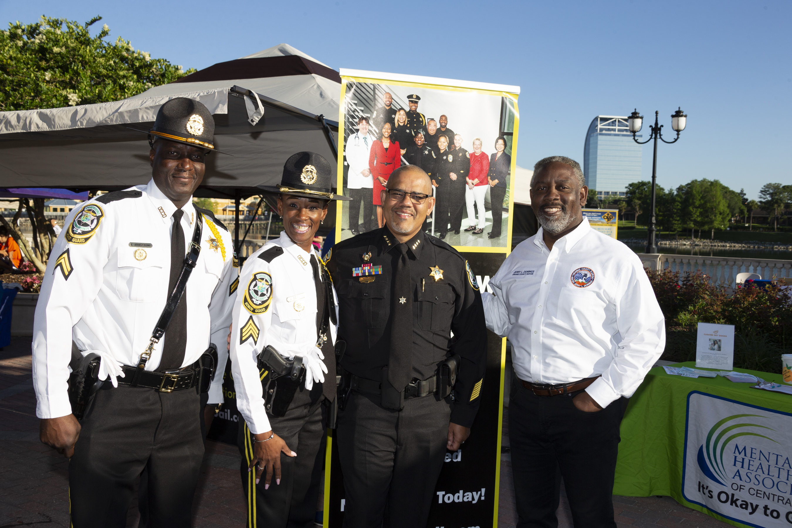 Orange County Corrections officers, Orange County Corrections Chief Louis A. Quiñones and Orange County Mayor Jerry L. Demings standing outside during the Greater Orlando NAMIWalks event .