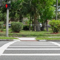 Crosswalk on a street corner leading to a park