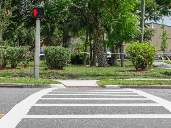 Crosswalk on a street corner leading to a park
