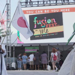 "Two women carrying flags of different nations on a pole. Behind them is a large screen that reads ""You can be You here. Fusion Fest."""