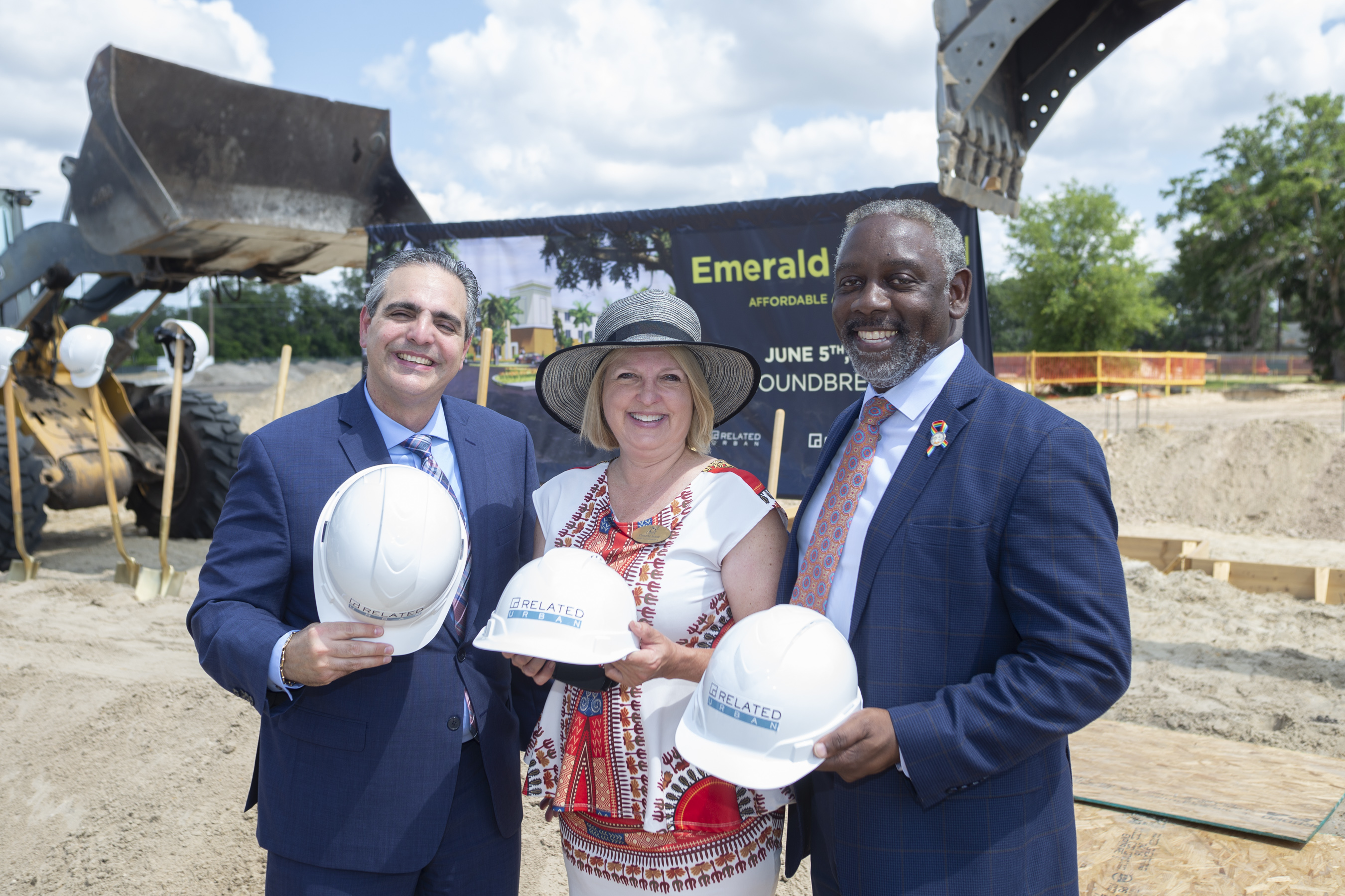 Three people holding hard hats at a groundbreaking outside.