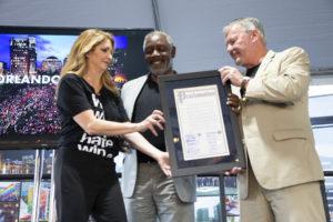El Alcalde Demings, el Alcalde Dyery Barbara Poma sostienen el documento enmarcado de la proclamación conjunta