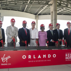 "Eight local and international leaders holding rubber mallets pretending to hammer down some stakes in front of a decorative piece of track. Below the track read the words ""Virgin Trains USA Orlando Groundbreaking. On Track to Red Hot Orlando."""