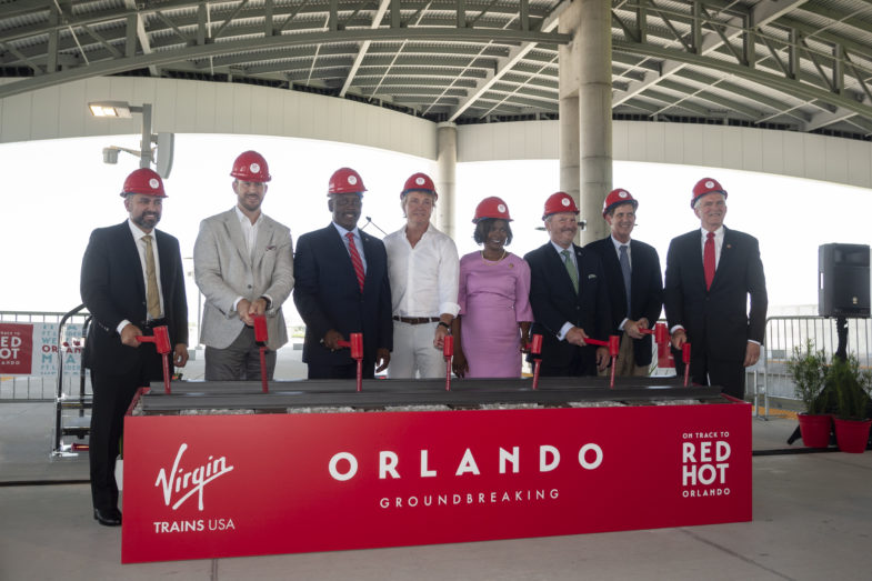 """Eight local and international leaders holding rubber mallets pretending to hammer down some stakes in front of a decorative piece of track. Below the track read the words """"Virgin Trains USA Orlando Groundbreaking. On Track to Red Hot Orlando."""""""