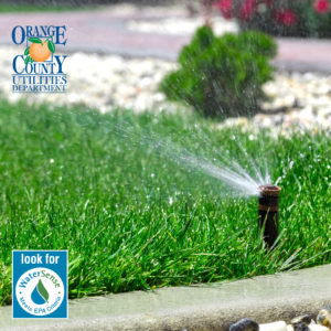 A picture of a sprinkler head watering a lawn with two logos.