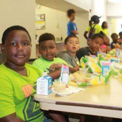 Niños pequeños sentados junto a la mesa disfrutando del almuerzo