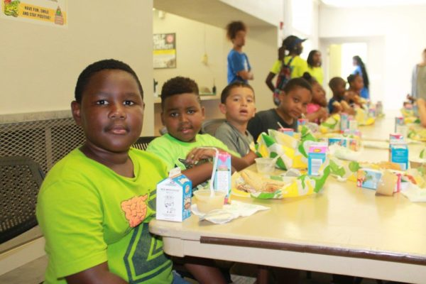 Young children sitting at a long table eating lunch