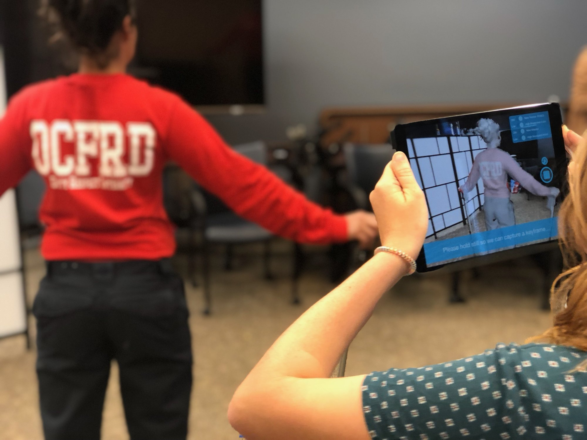 Technician holding a scanning device as she scans a female firefighter