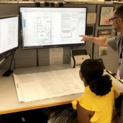 Dos empleados en un escritorio analizan los planos de construcción sobre un papel y en el monitor de la computadora