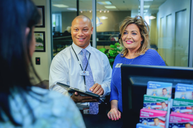 Dos empleados reciben a una clienta con una sonrisa