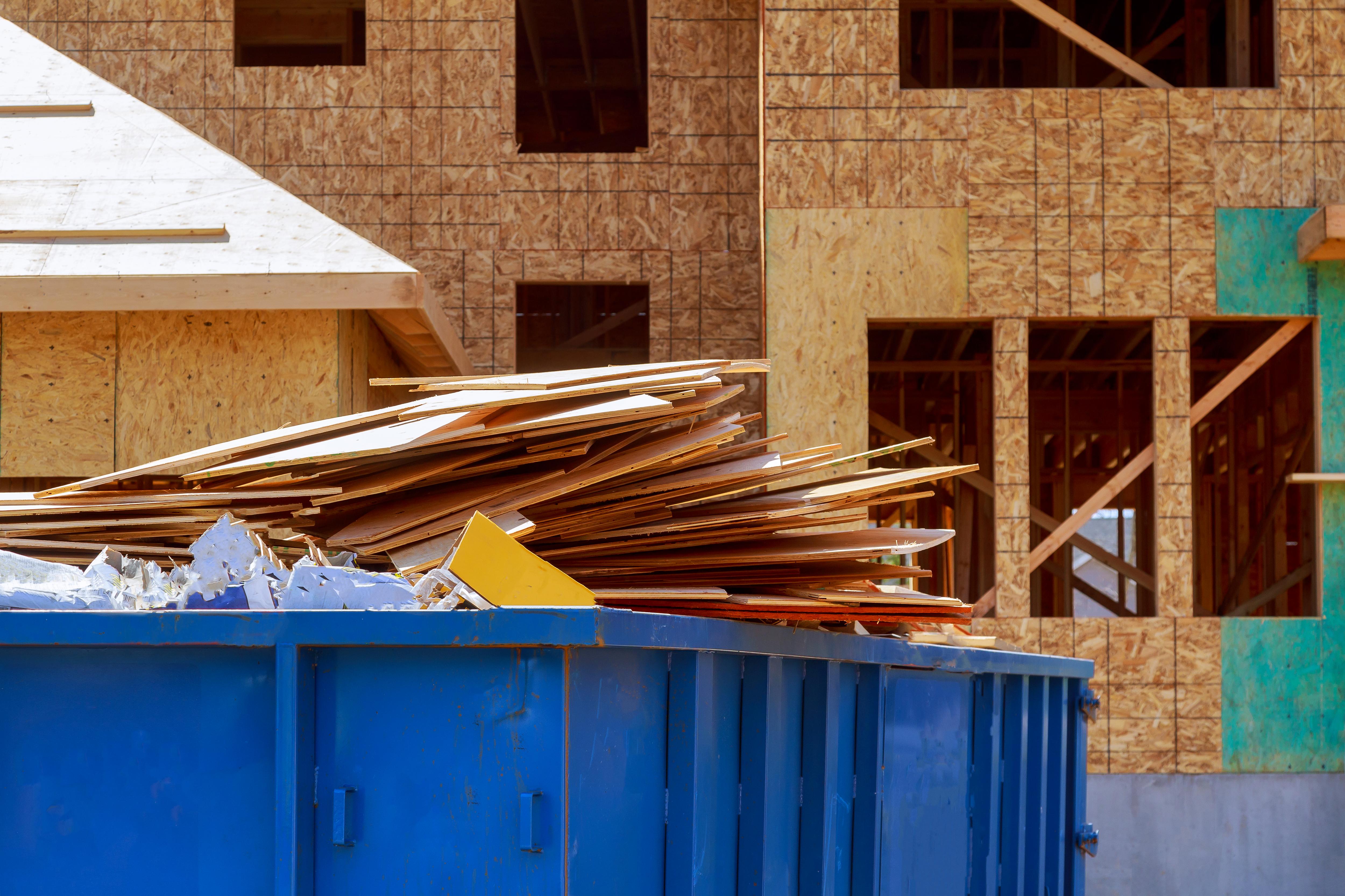 Sitio de construcción con basura dentro de un contenedor grande