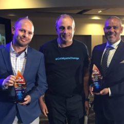 Tres hombres posan para la foto con sus premios