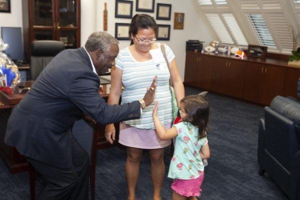 El Alcalde Demingschoca los cinco con una pequeña mientras su madre permanece junto a ella. Están en la Oficina del Alcalde.