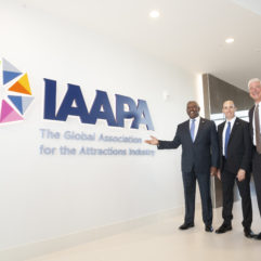 Mayor Demings and two other men standing next to a wall with the IAAPA logo on it
