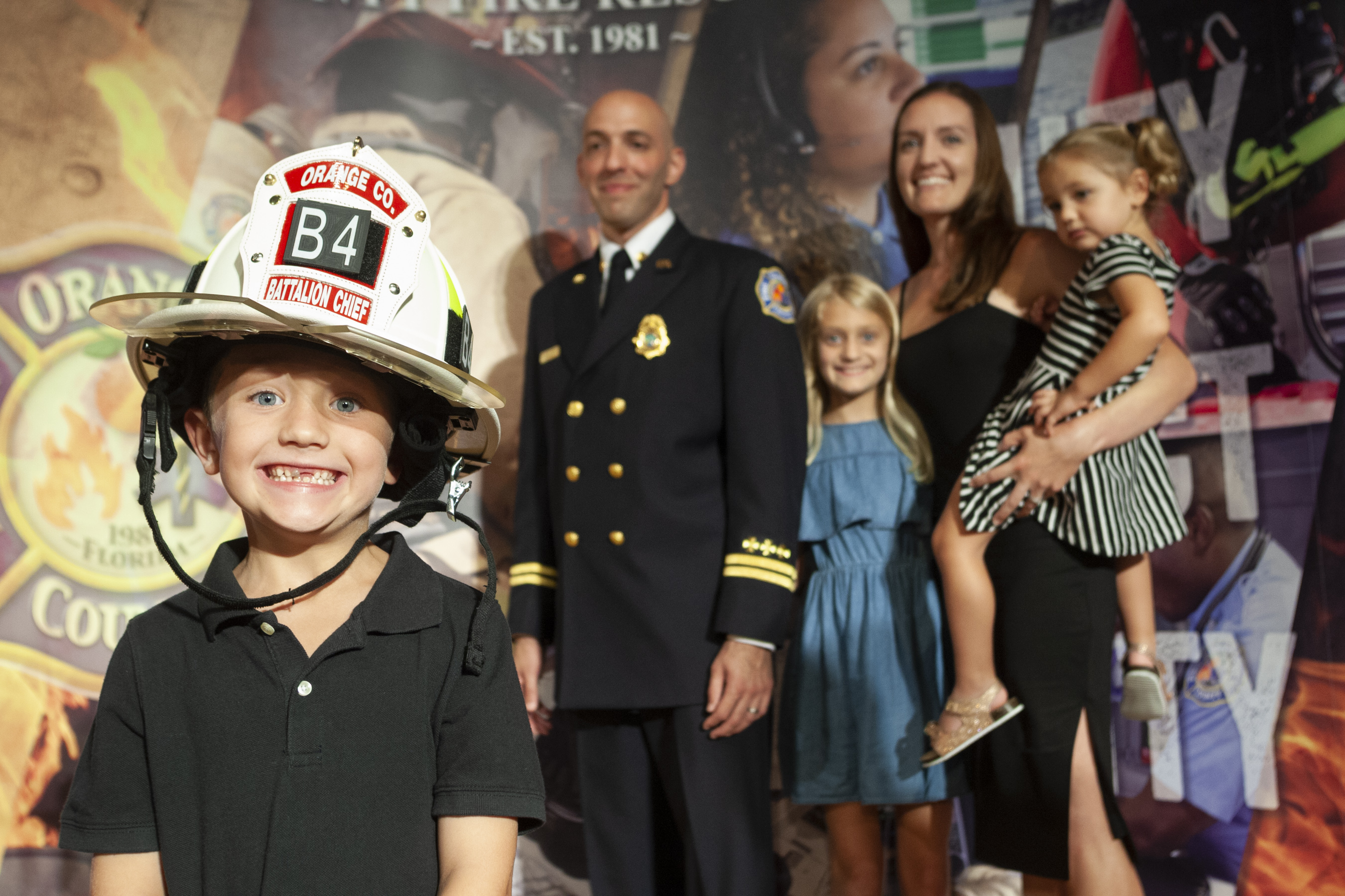 Un muchacho con casco de bombero sonriendo. Su familia permanece parada en el fondo.