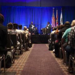 El Alcalde Demings y Jason Reynolds sentados en sillones en el escenario ante una multitud que escucha atentamente el debate