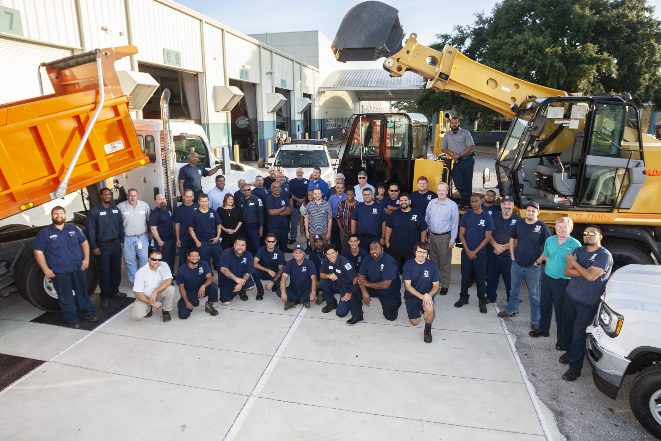 Group photo of the men and women who make up the Fleet Management team. They stand among different vehicles, including trucks