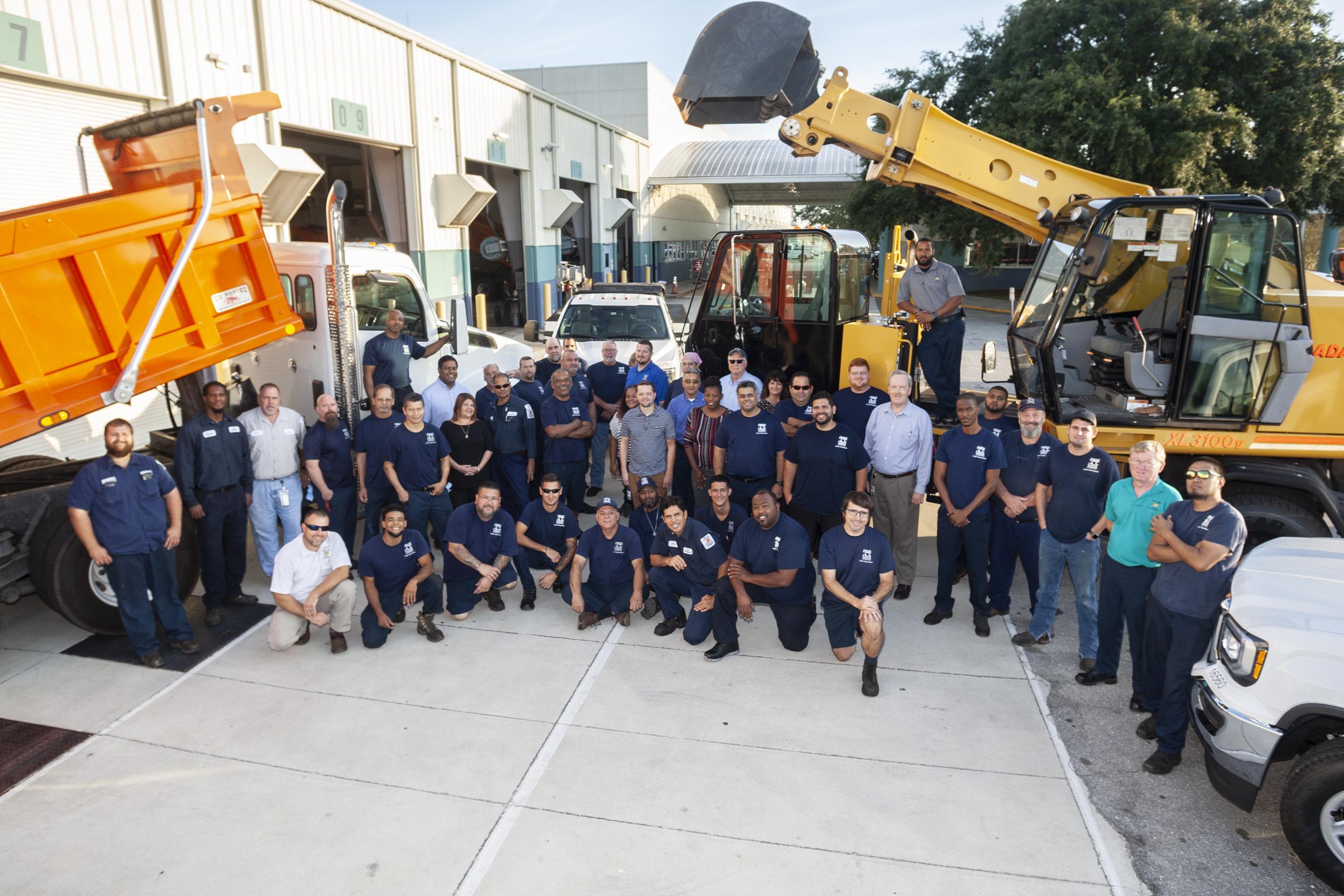 Foto grupal de los hombres y muejres que conforman el equipo del Manejo de Flotas. Posan entre varios vehículos, incluidos camiones