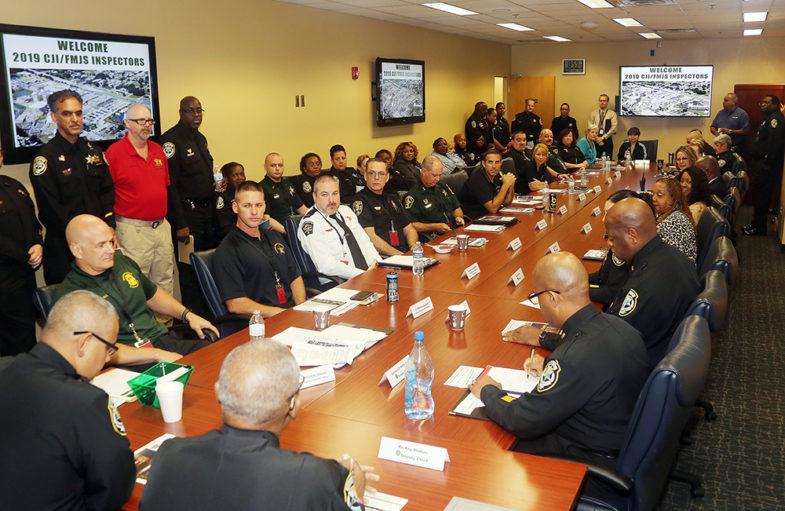 Un grupo numeroso de líderes de correccionales sentados alrededor de una mesa de conferencia.